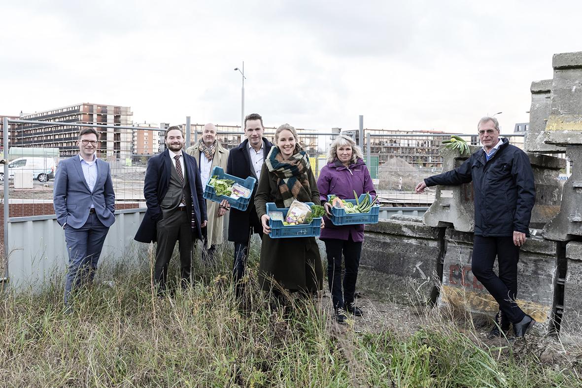 Groep mensen met kratten vol groente op een bouwveld