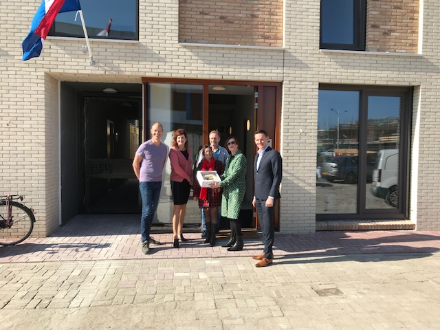 Projectwethouder Martina Huijsmans overhandigt een welkomsttaart aan nieuwe bewoners in de Coendersbuurt.