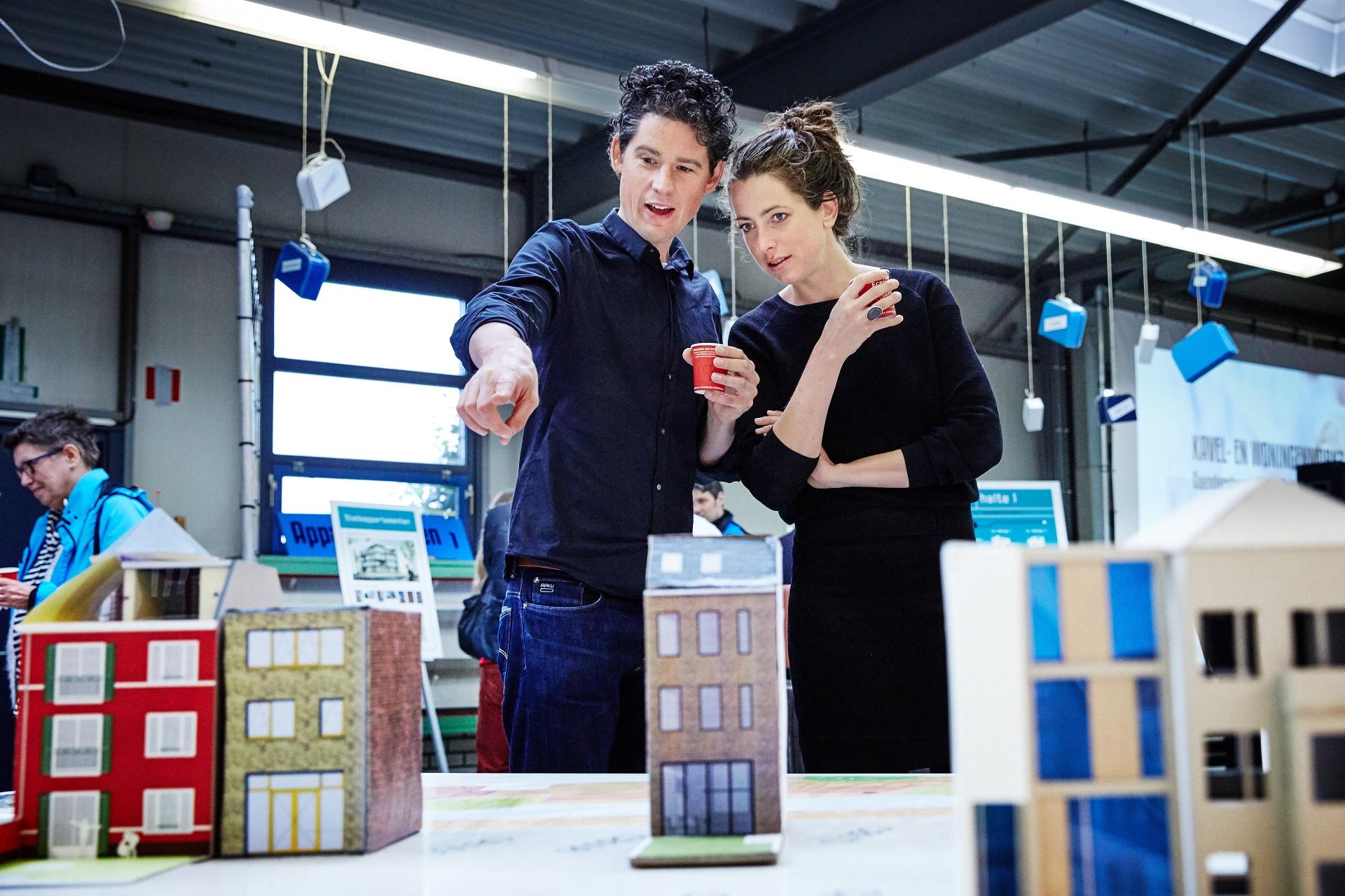 Twee mensen kijken naar een maquette van gebouwen in Nieuw Delft