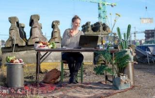 Foto van initiatiefnemer IChange aan een tafel met laptop omringd met voedsel