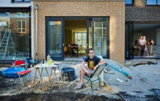Foto van een zelfbouwer tussen de bouwmaterialen in zijn tuin.