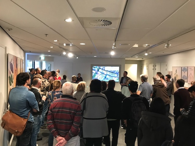 Mensen kijken naar presentatie over de zelfbouwkavels op veld 6 in Nieuw Delft