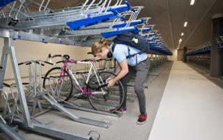 Jongen zet fiets op slot in de fietsenstalling