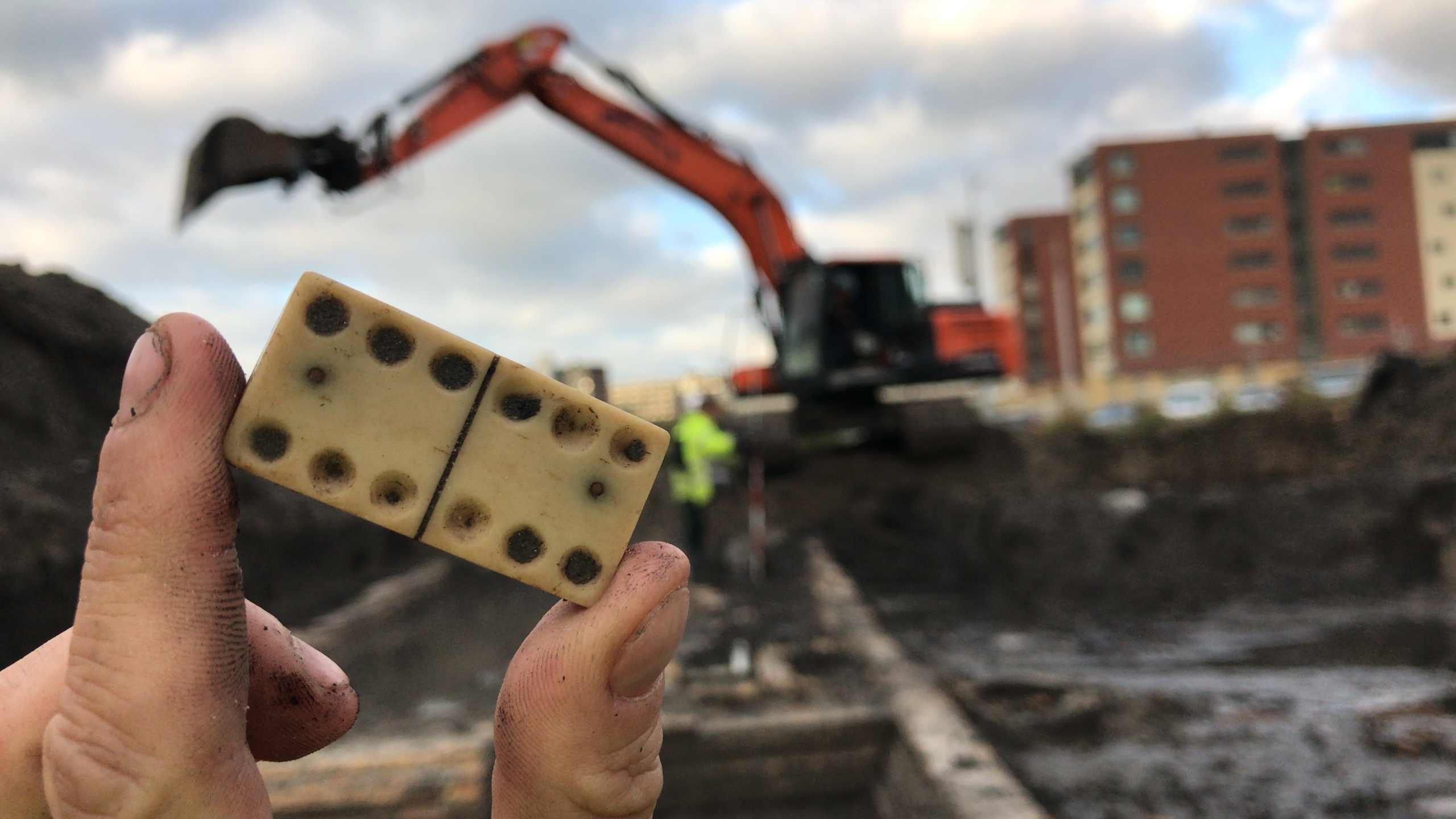Een hand met dominosteen met op de achtergrond de archeologische opgraving in Nieuw Delft