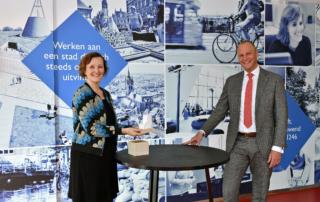 Wethouder Huijsmans en directeur de Pon staan bij een tafel met een klein schaalmodel van het toekomstige gebouw