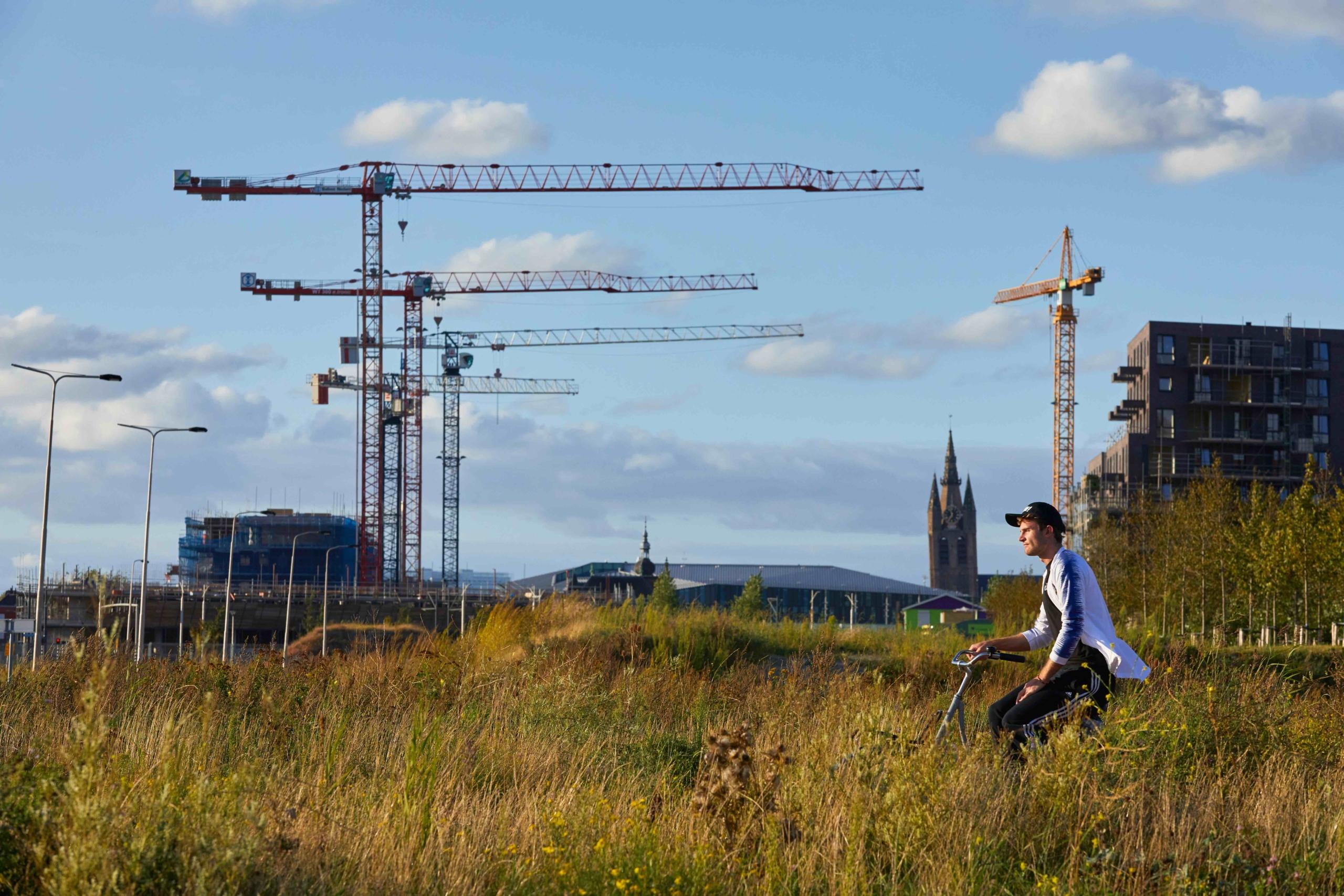 Een fietser fietst door het braakliggende gebied van Nieuw Delft. Op de achtergrond drie bouwkranen.