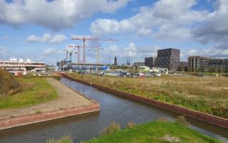 lege bouwgrond met op de achtergrond de skyline van de Delftse binnenstad en enkele bouwkranen