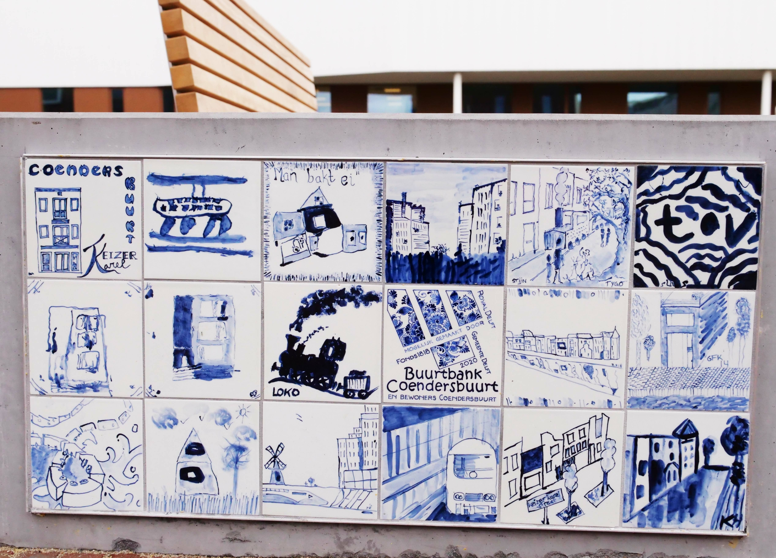 beschilderde delftsblauwe tegels op de buurtbank in de Coendersbuurt, met tekeningen van huizen en treinen.