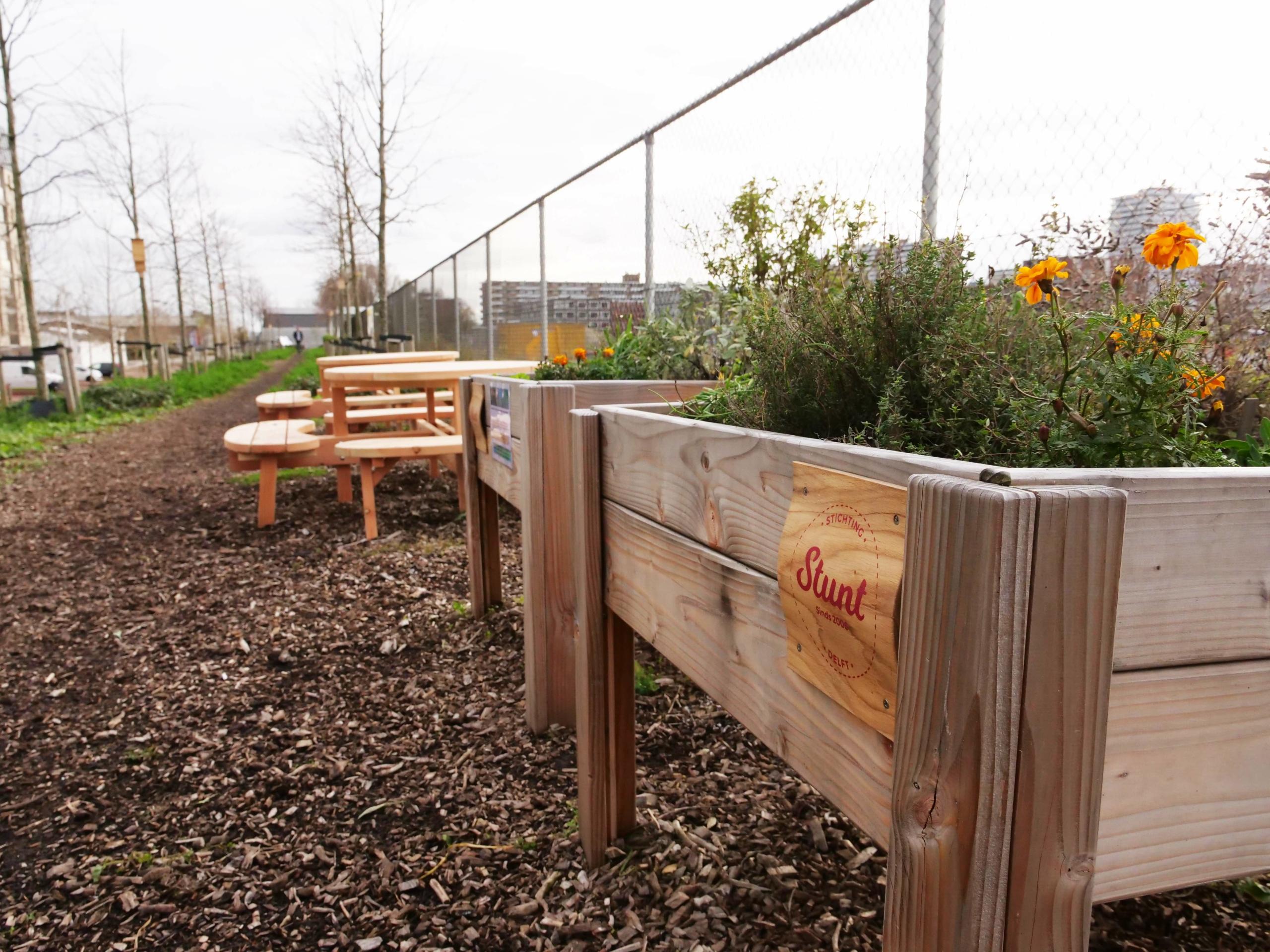 bloembak en picknickbankjes in de parkstrook in Nieuw Delft