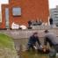 wethouder en initiatiefnemer staan met laarzen aan in het water om de eerste planten te water te laten