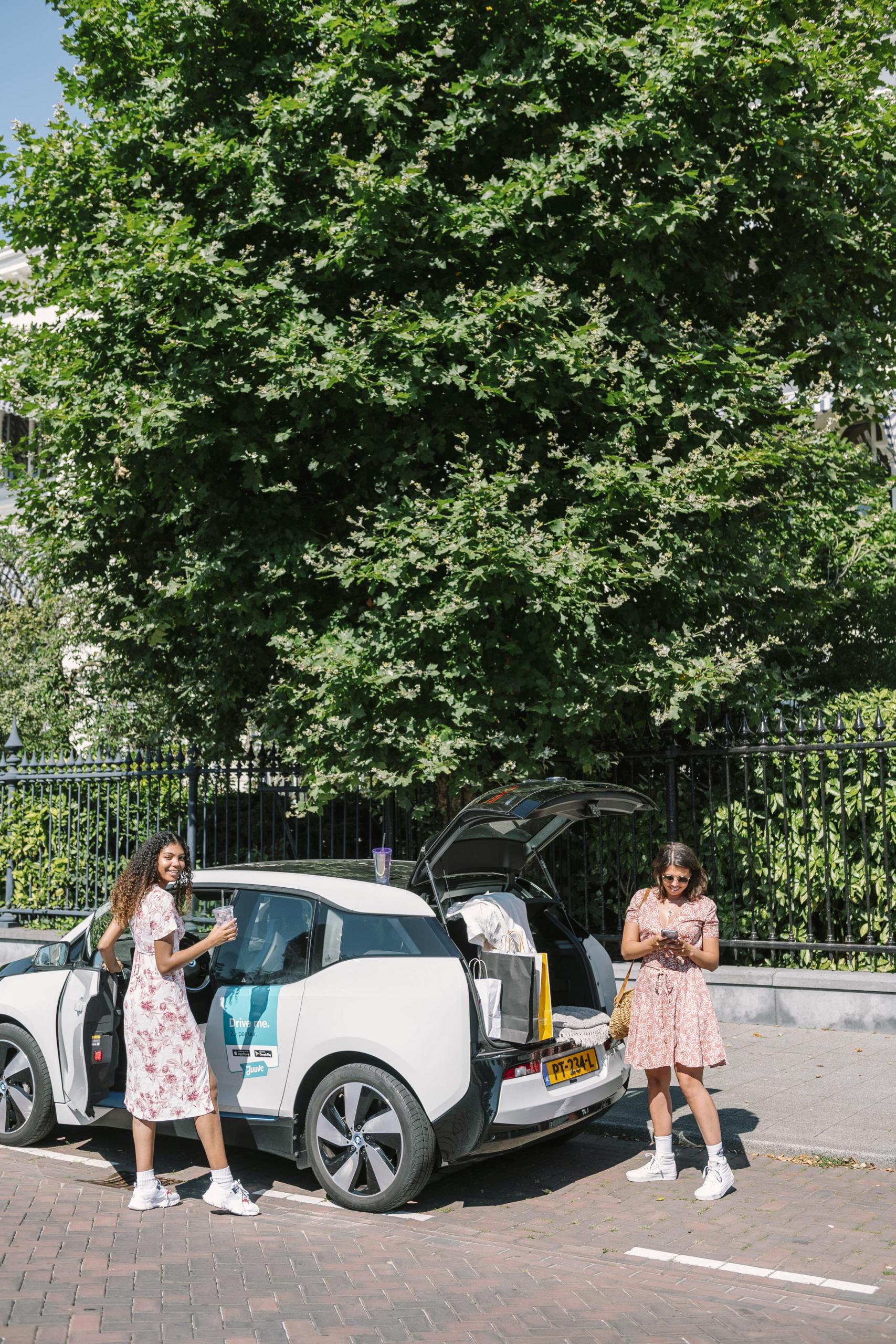 twee vrouwen staan bij een deelauto
