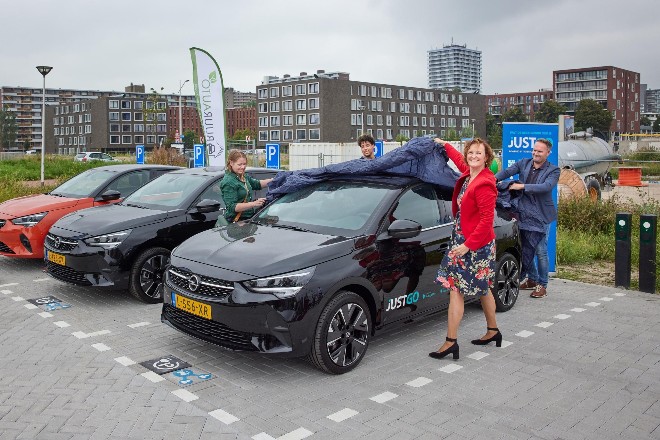 Wethouder Huijmans naast een deelauto op de Delft Mobility hub aan de Engelsestraat